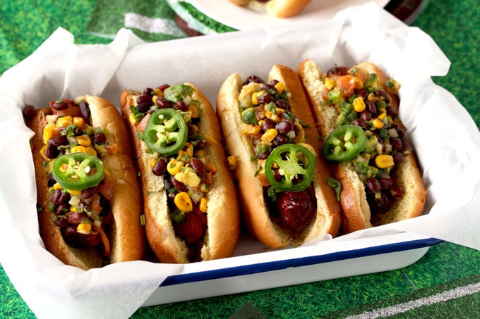 A tray filled with four Southwest Bacon Wrapped Hot Dogs garnished with cilantro and jalapeno slices set on a green tablecloth
