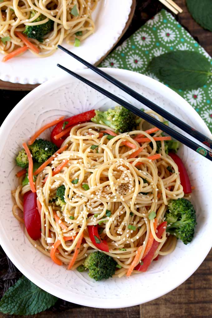 Top view of a bowl with Asian Peanut Sesam Noodles in a white bowl next to black chopsticks.