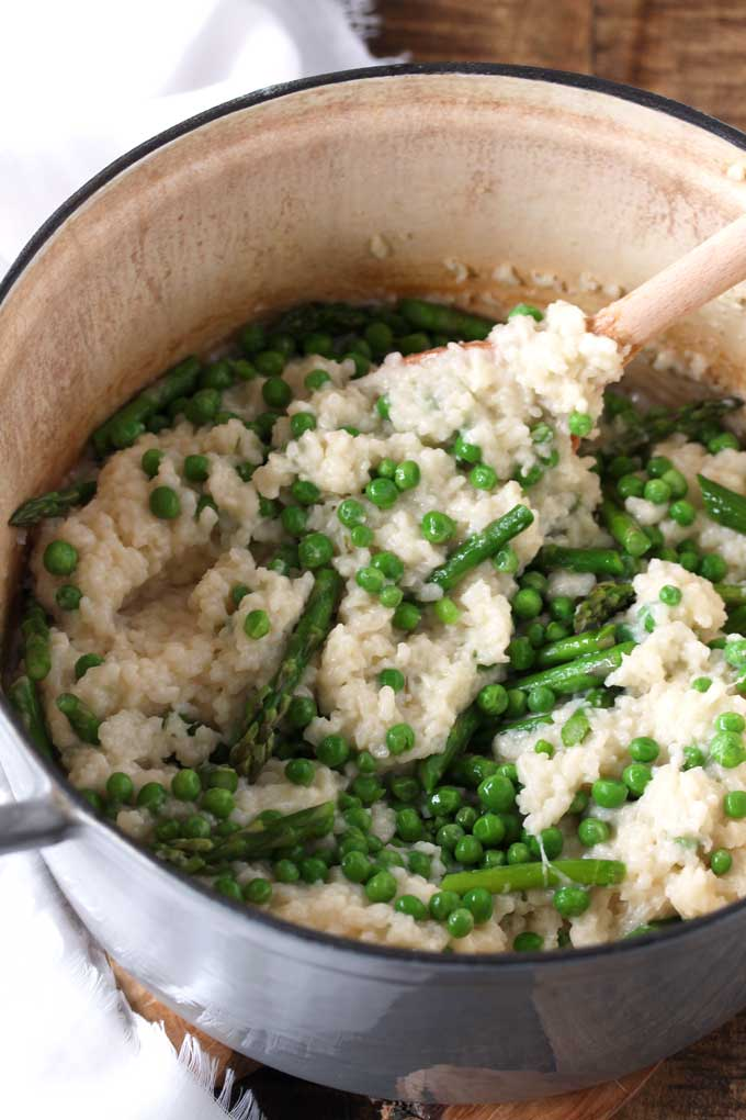Risotto mixed with asparagus and peas in a Dutch oven