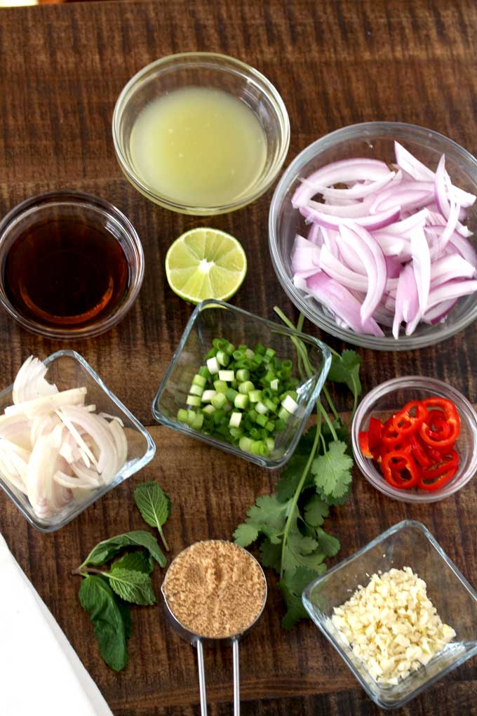 Ingredients to make Thai Larb Salad on a wooden counter.