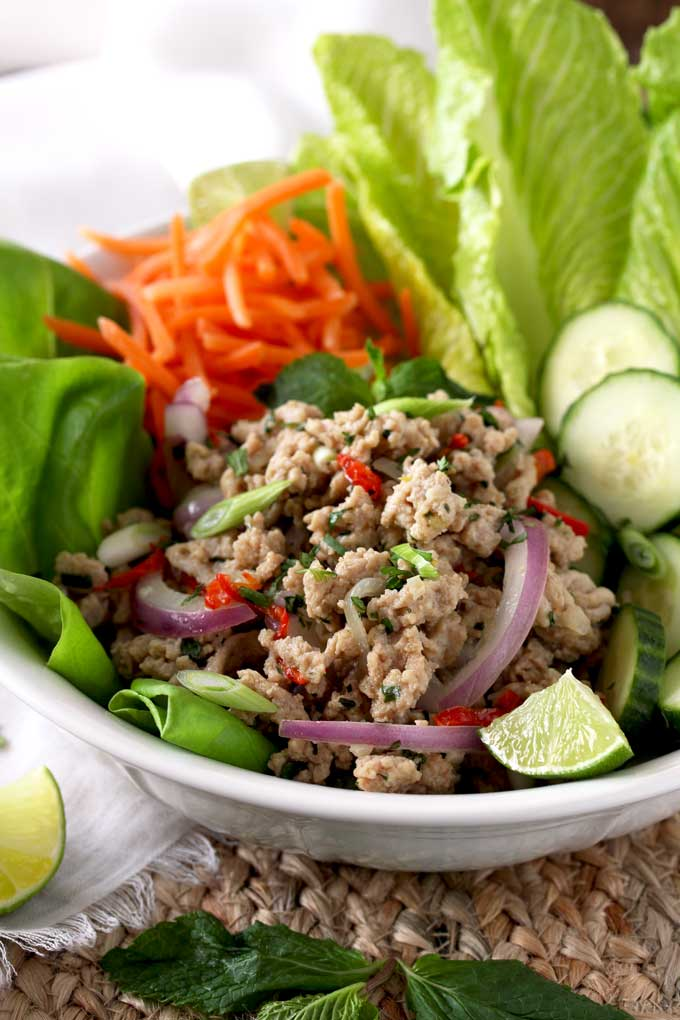 view of a white bowl filled with Larb Salad. With Romaine lettuce, Butter Lettuce, shredded carrots and sliced cucumbers.