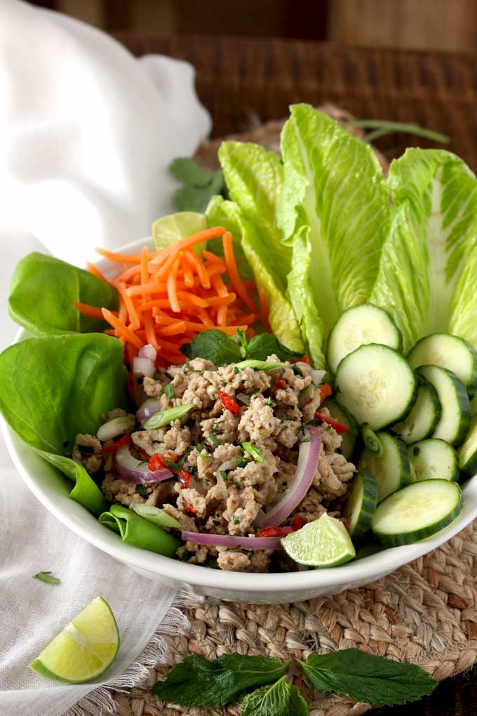 A white bowl of Thai Chicken Larb Salad surrounded with lettuce leaves, shredded carrots, sliced cucumbers and lime slices.