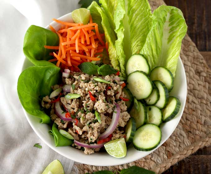 Top view of a white bowl filled with Larb Salad. With Romaine lettuce, Butter Lettuce, shredded carrots and sliced cucumbers.