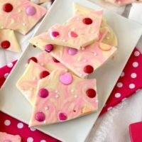 Pieces of white chocolate valentine's bark on a rectangular white plate.