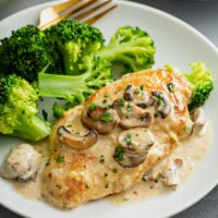 Chicken breast cutlet in mushroom cream sauce served with broccoli on a white plate