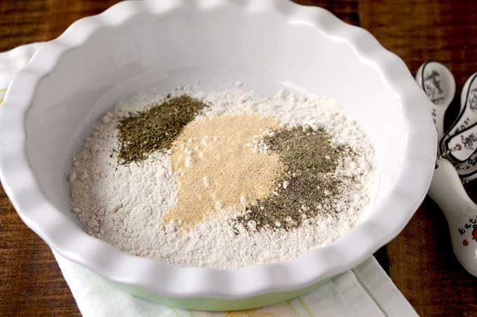 In this photo a shallow bowl with all-purposed flour, garlic powder, black pepper and Italian seasoning.
