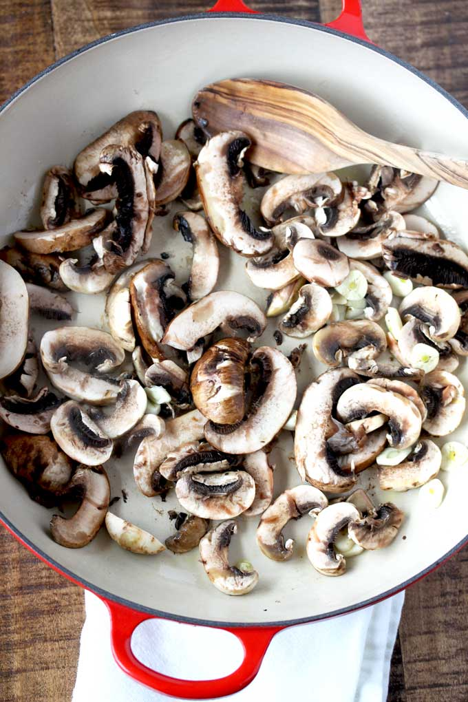 Sliced mushrooms and garlic cooking inside a skillet