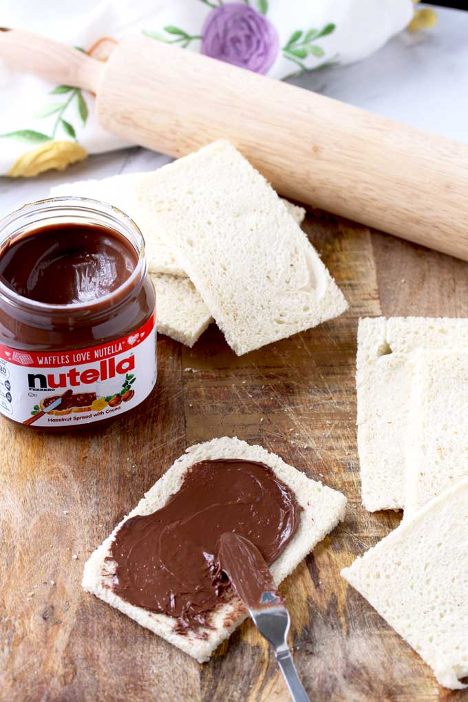 Flattened bread slices are spread with nutella