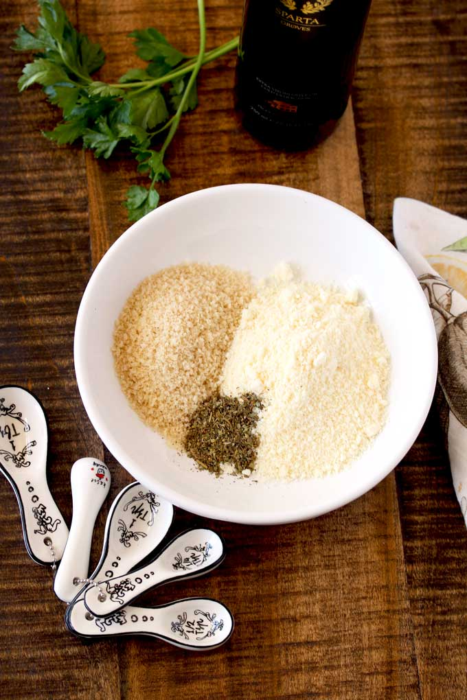 In a white bowl the ingredients for the Parmesan/ Panko crumb mixture