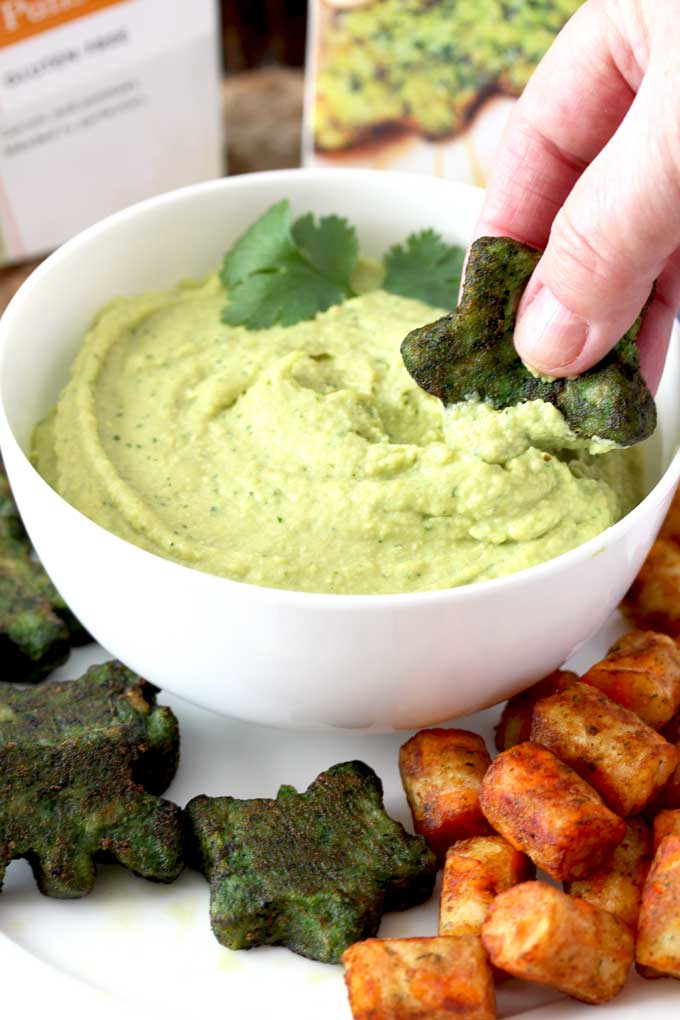 A spinach little is dipped in creamy avocado hummus