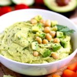 Avocado Hummus in a white serving bowl garnished with avocado and chickpeas.