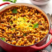 Chili macaroni and cheese or chili mac in a red Dutch oven pot