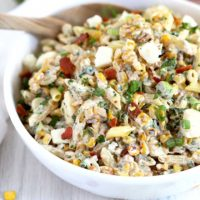 Mexican Street Corn Pasta Salad in a white bowl with a serving spoon.