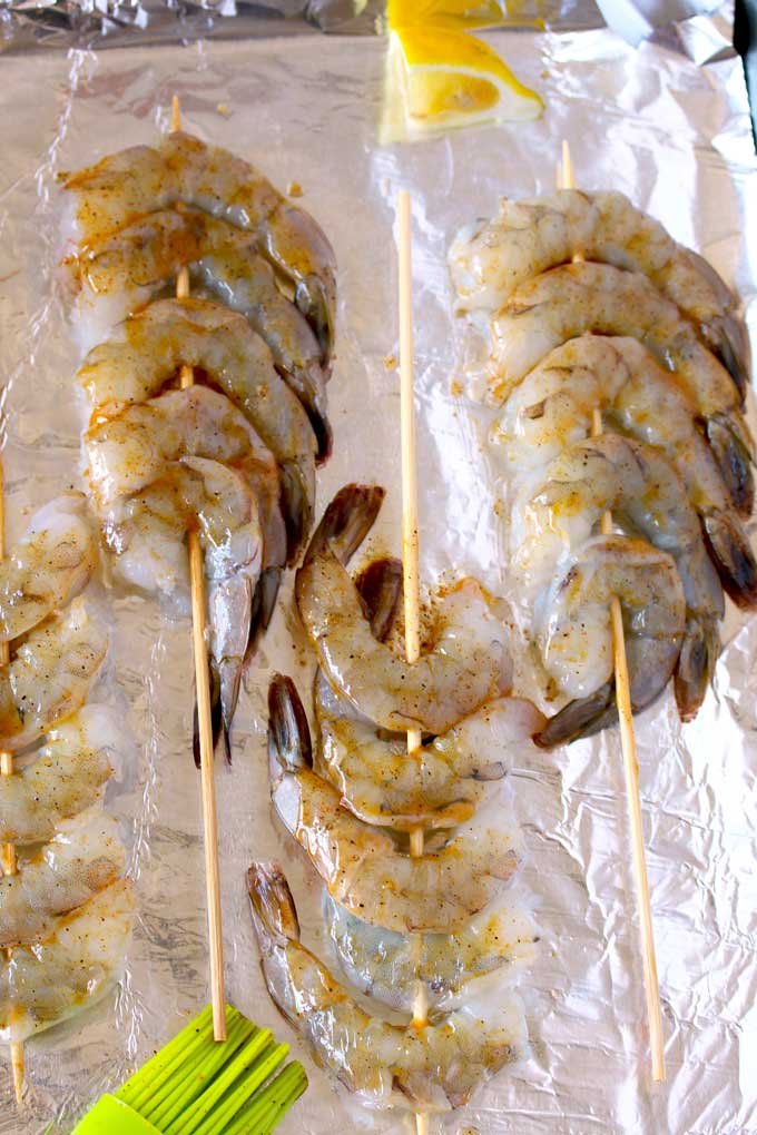 Raw shrimp skewered on a sheet pan