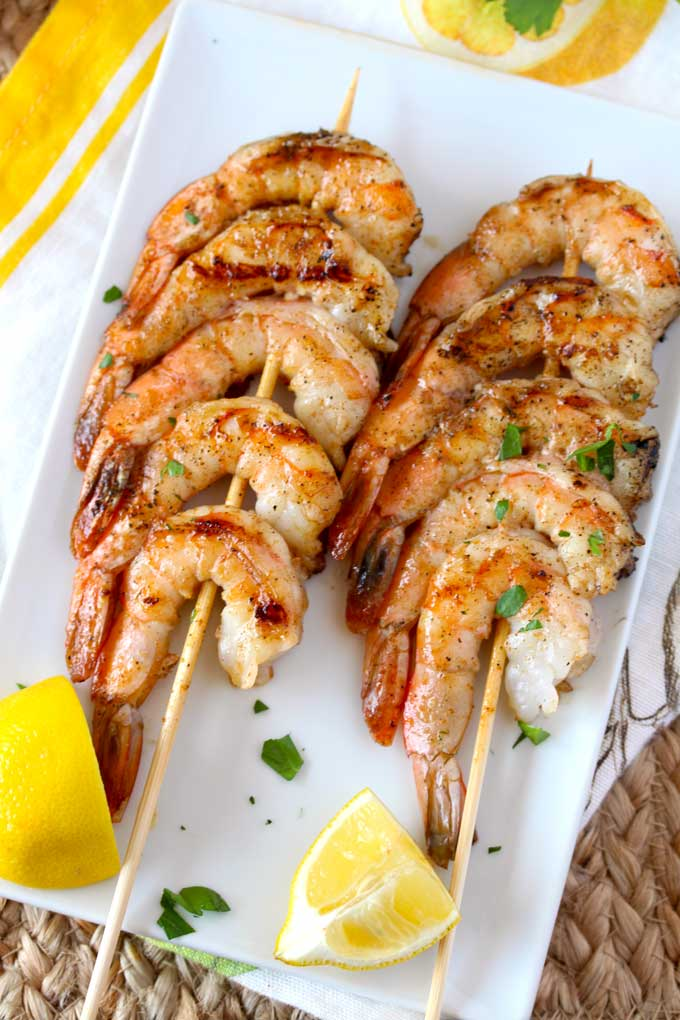 Two shrimp skewers on a white plate