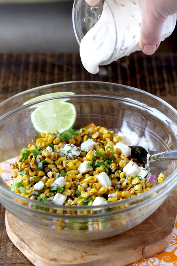 Creamy lime-infused dressing is poured over the Mexican Street Corn Salad