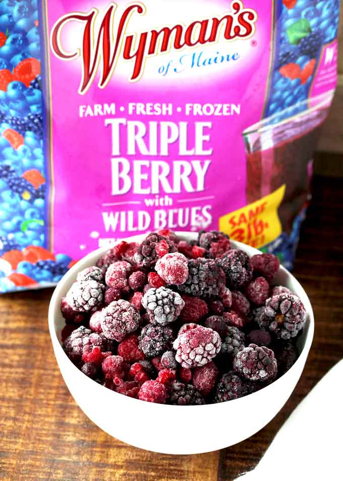 Pictured here a white bowl with frozed mixed berries next to a bag of frozen berries.
