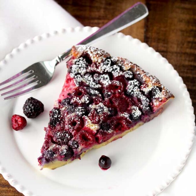 A slice of mixed berry clafoutis on a white plate
