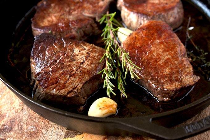 Four filet mignon steaks in a cast iron skillet