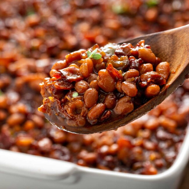 Homemade baked beans served with a wooden spoon from a white baking dish