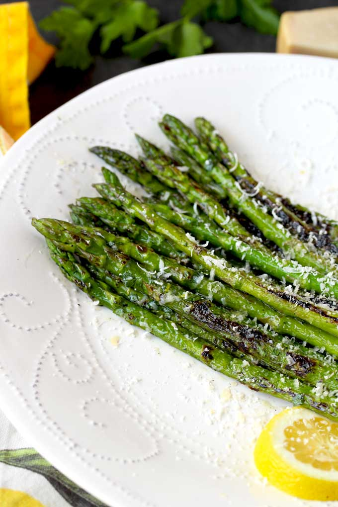 A bunch of grilled asparagus on a white serving plate