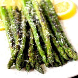 Grilled Asparagus on a white plate with Parmesan cheese
