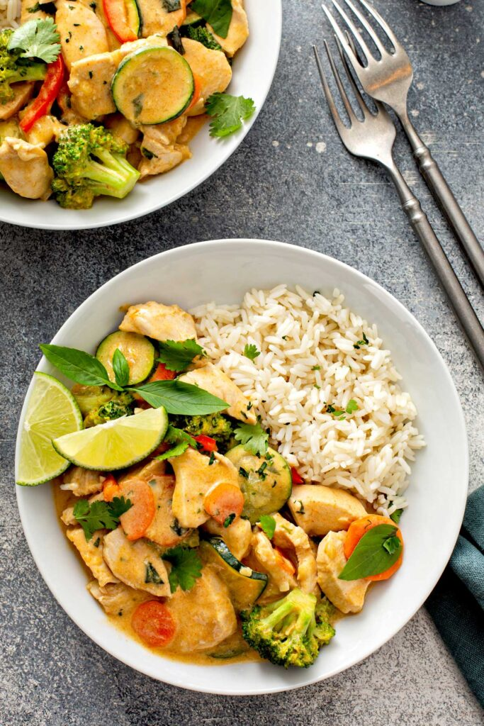 Bowls filled with Thai red curry with coconut milk and veggies served with rice.