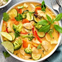 Bowl of curry Thai chicken with vegetables and fresh herbs