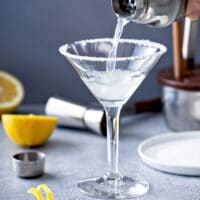 Cocktail shaker pouring a lemon drop cocktail in a martini glass