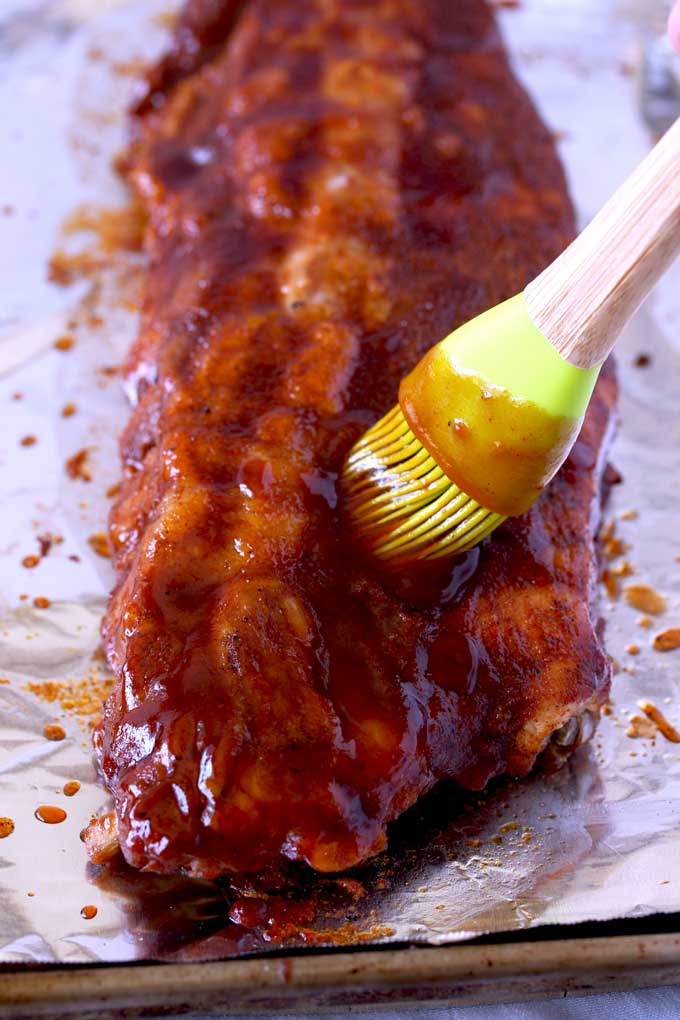 Cooked ribs are brushed with BBQ sauce