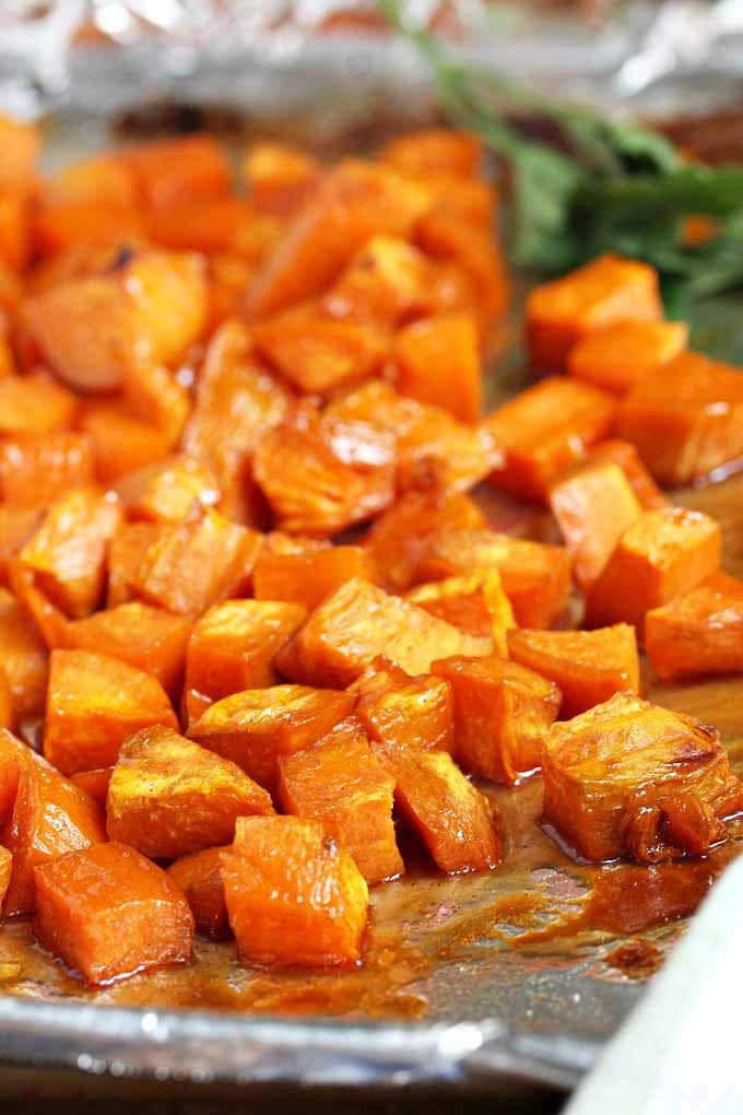 Roasted maple sweet potatoes on a sheet pan.