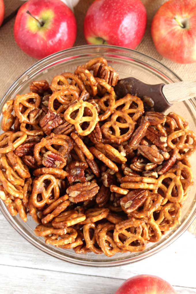 A bowl filled with pretzels and pecans.