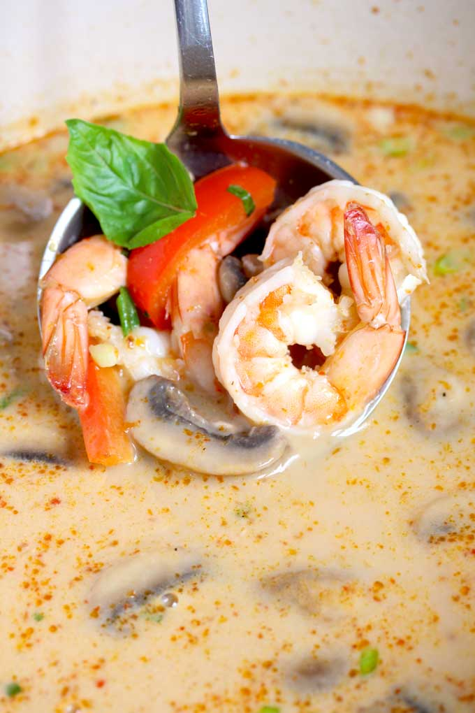 A laddle of coconut curry soup with shrimp.