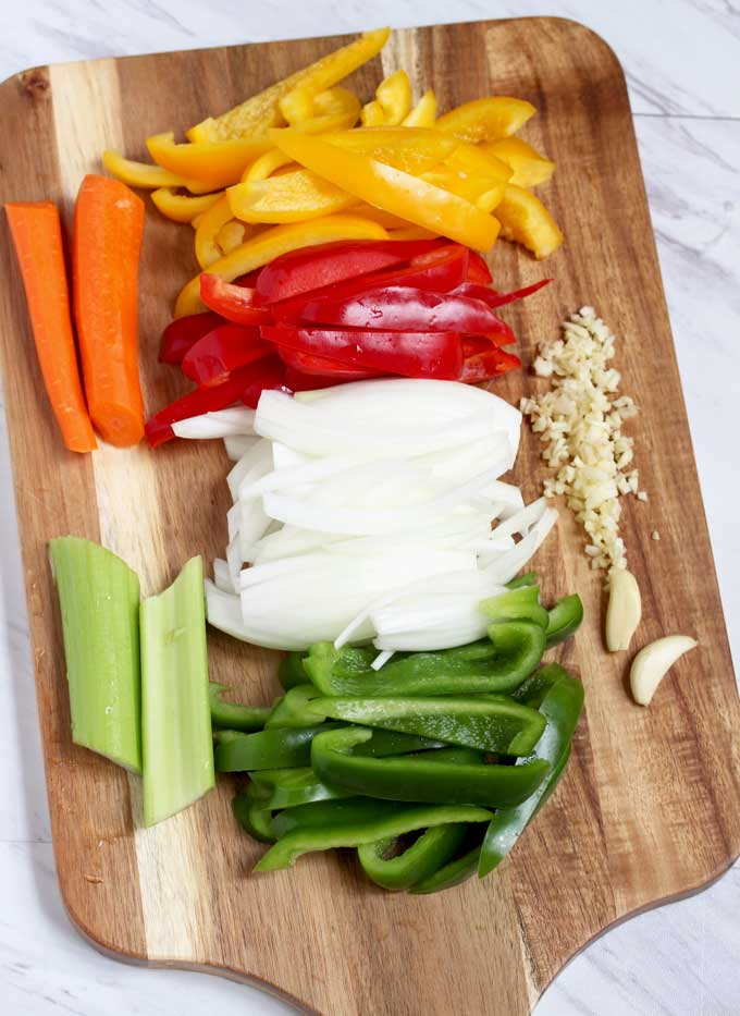 Vegetables to make Ropa Vieja .Chopped bell peppers, onions, carrots, celery and minced garlic on a cutting board.