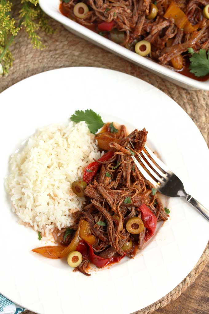 Cuban Ropa Vieja served with rice on a white plate.