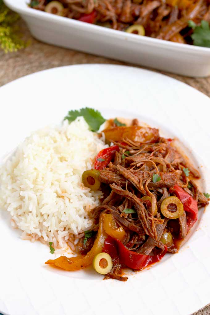 Cuban Ropa Vieja served with white rice on a white plate.