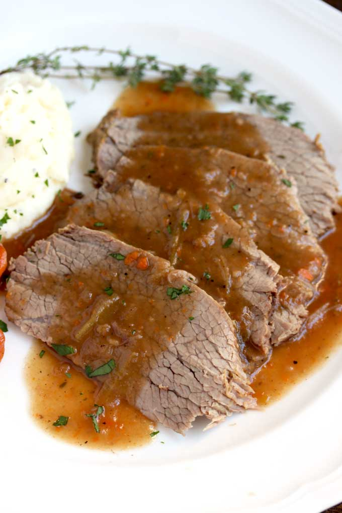 Close up view of sauerbraten slices on a white plate