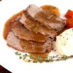 Slices of saurbraten with mashed potatoes and carrots on a white plate.