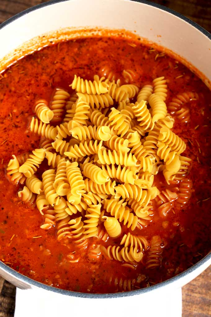 Mixture of sausage, pepperoni, saute vegetables pasta sauce topped with uncooked noodles.