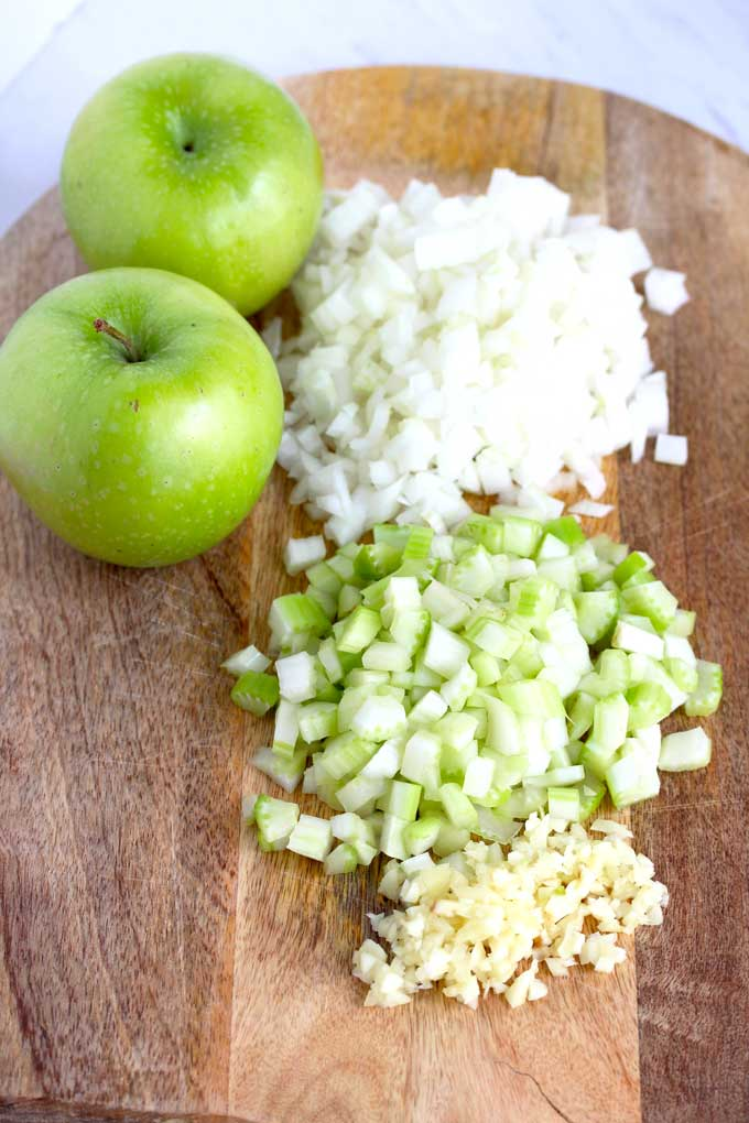 Ingredients to make this Apple and Sausage Stuffing Recipe. Chopped onions, apples and minced garlic on a cutting board.
