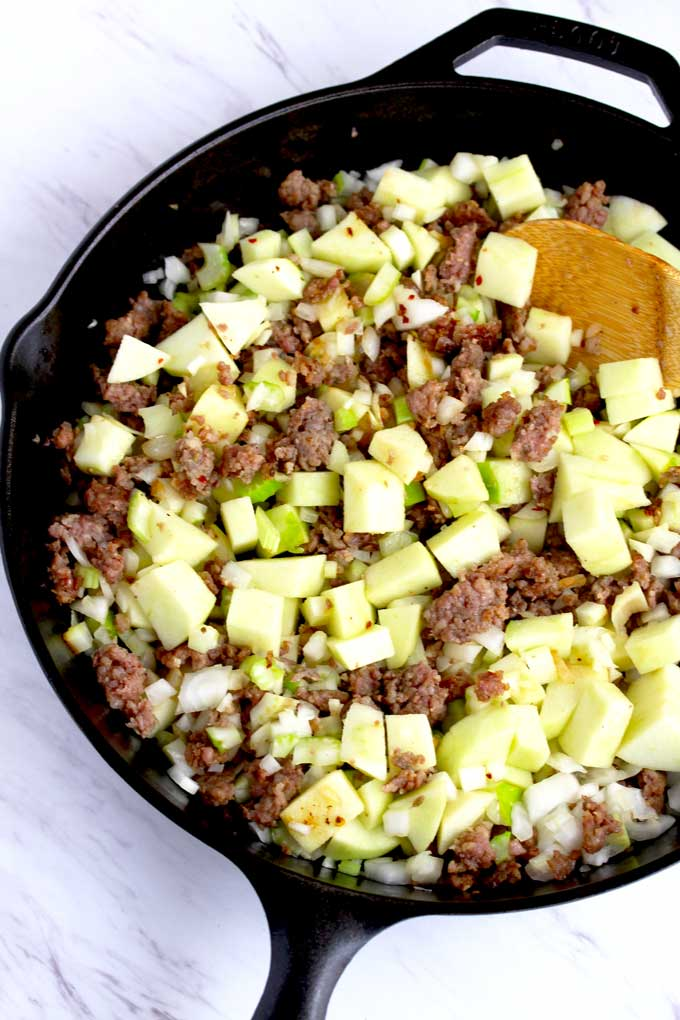 Sausage, chopped onions and apples on a skillet.