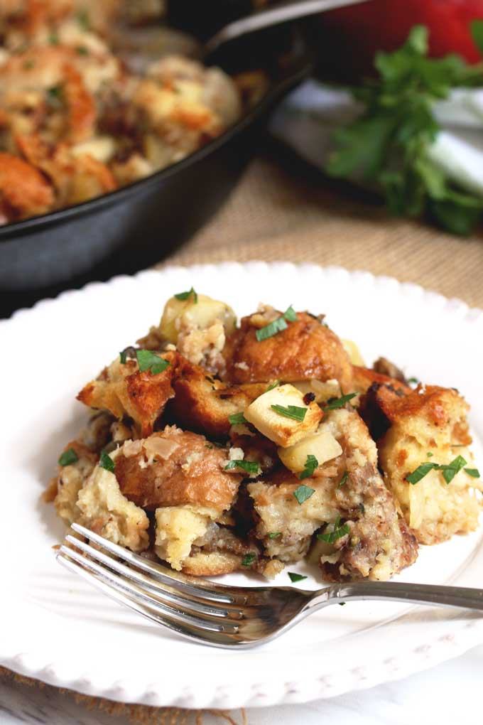 Apple ans sausage stuffing on a white plate.