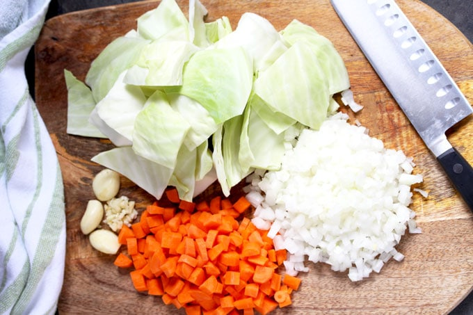 Chopped cabbage, chopped onions, diced carrots and garlic on a cutting board.