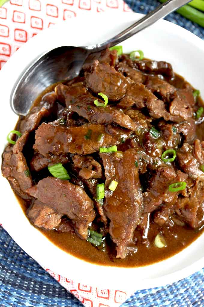Top view of sliced flank steak in Chinese sauce on a white bowl.