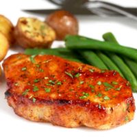 Oven Baked Pork Chops with roasted potatoes and green beanson a white plate