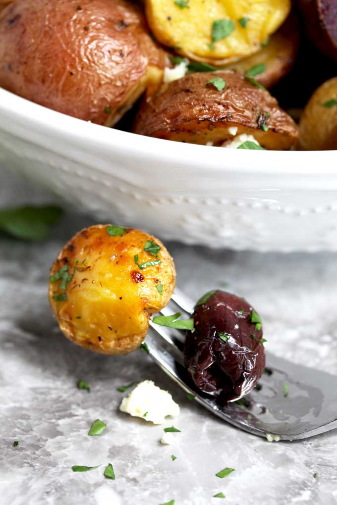 A golden Greek potato with a kalamata olive and feta cheese.