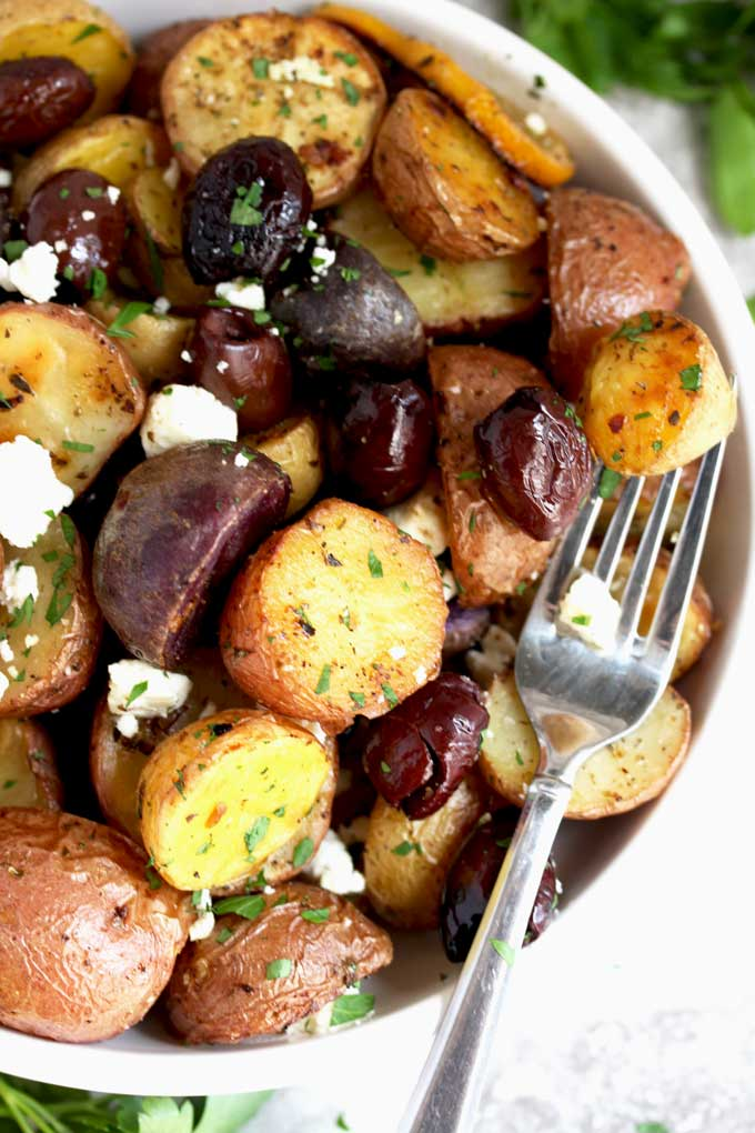 Greek Potatoes in a white serving bowl
