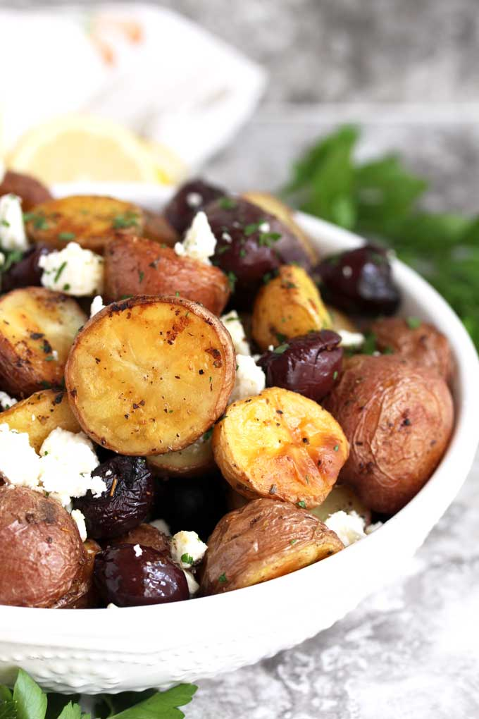 Greek Potatoes with Kalamata olives and feta cheese in a white bowl.