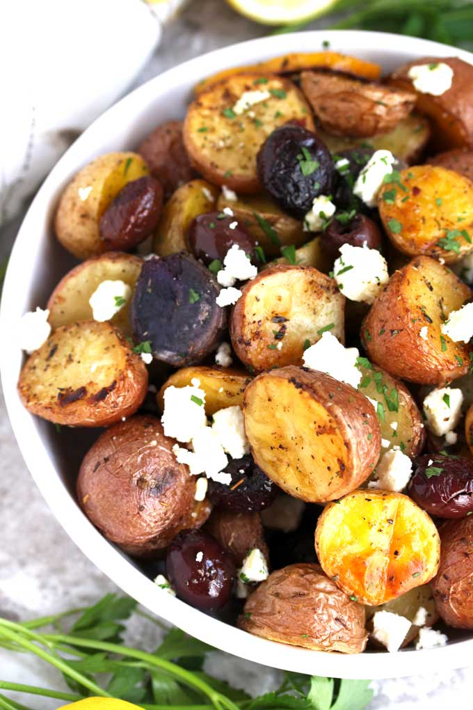 Pictured here a white bowl filled with Roasted Greek Potatoes.