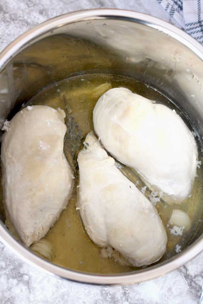 Cooked chicken breasts and broth inside the instant pot